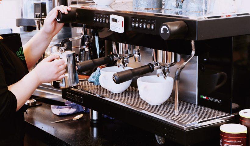 kaffeemaschine-schwarz-mit-frau-und-zwei-tassen